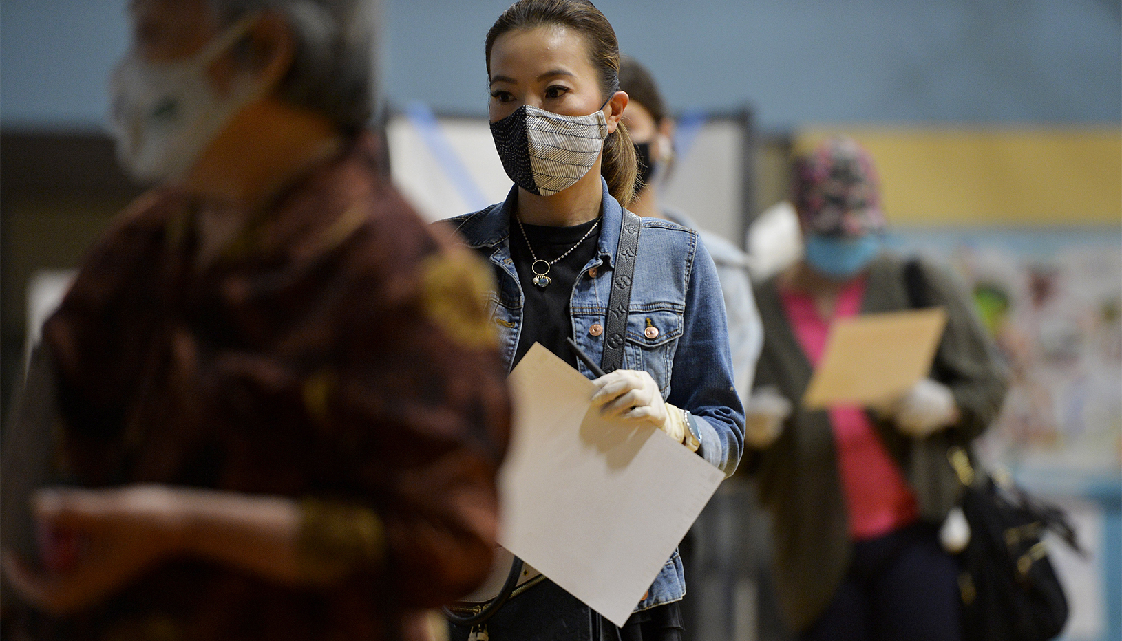Woman in face-mask in line to vote