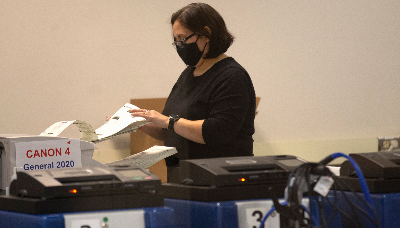 A poll worker scans ballots at the Maricopa County Recorders Office where votes in the general election are being counted, in Phoenix, Thursday, Nov. 5, 2020.
