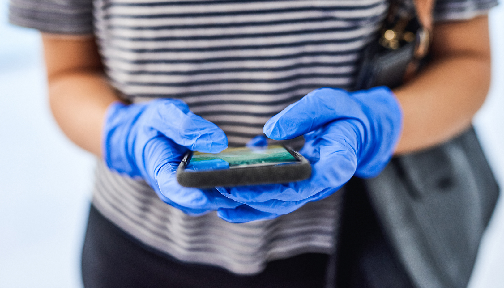 person wearing surgical gloves holding a smart phone