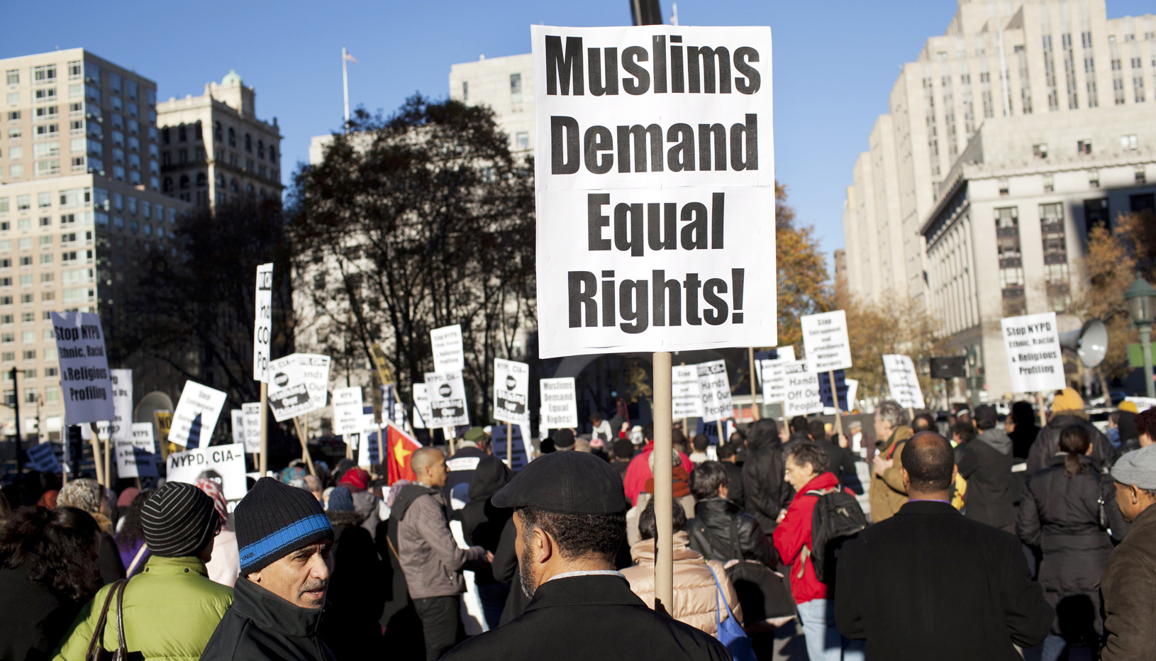 "a protestor holds a sign that reads ""Muslims demand equal rights!"""