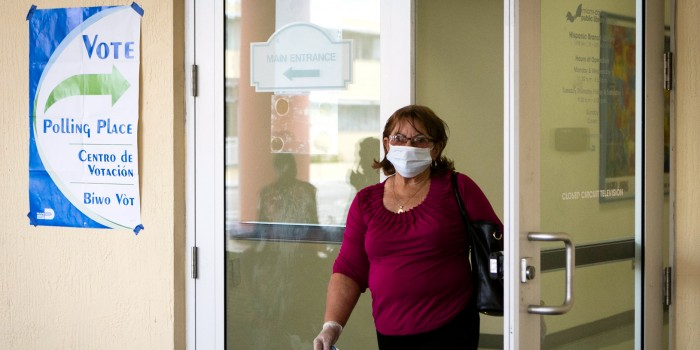 Voter in surgical mask exiting a polling place.
