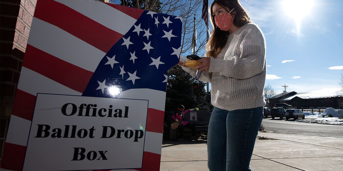A person standing in front of a ballot drop box.
