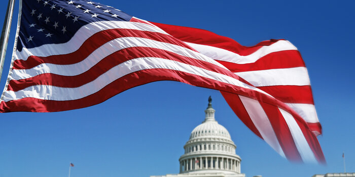 The United States flag flying in front of the Capitol building.