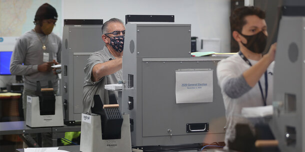 Three people in masks using voting machines to vote.
