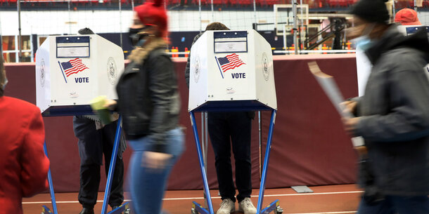 person walking past two voting booths while wearing a mask.