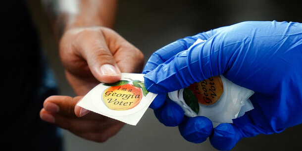Poll worker wearing a glove is handing a voter a Georgia sticker.